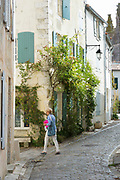Typical street scene quaint house with shutters traditional architecture, woman walking, St Martin de Re, Ile de Re, France