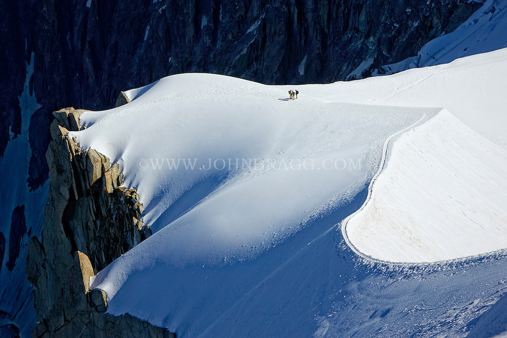 View of trio of hikers walking across the French Alps - Chamonix, France.