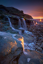 A blade of sunlight cuts across the water falls at Osmington Mills Dorset
