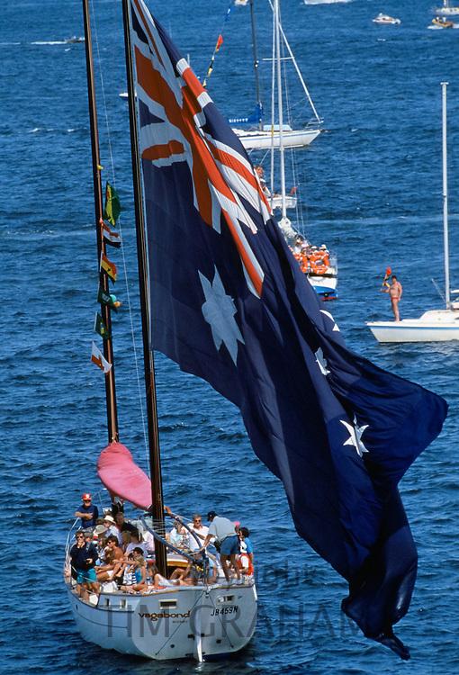 Australian flag being flown in boat by Sydney Harbour for Australia's Bicentenary, 1988