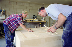 Man with learning disability and colleague doing woodwork; assembling wooden wardrobe,
