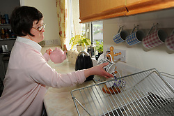 A women with Learning Disabilities makes a cup of tea in the kitchen of her supported housing flat; Skipton; North Yorkshire,UK