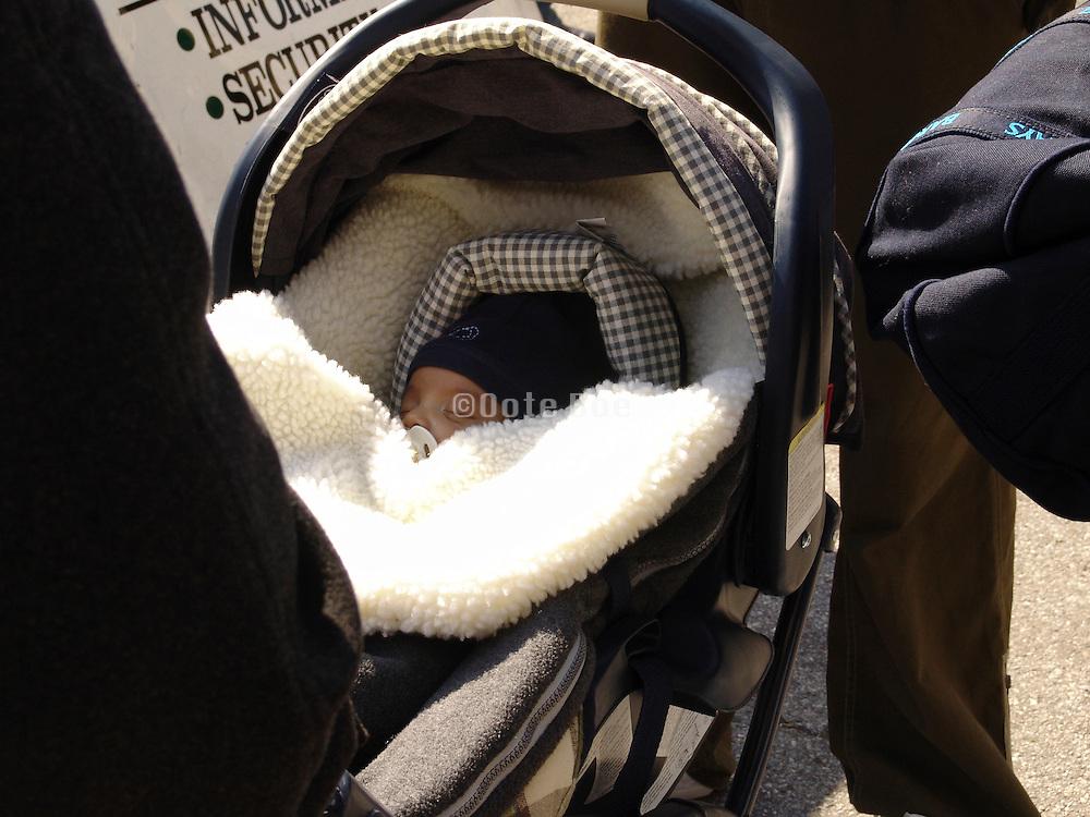 A toddler asleep in his stroller