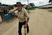 An older gentleman heads to his field with some posts which he will use to repair the fence around his property in Guaimaca, Honduras.  Honduras is considered the third poorest country in the Western Hemisphere (Haiti, Nicaragua). With over 50% of the population living below the poverty line and 28% unemployed, Hondurans frequently turn to illegal immigration as a solution to their desperate situation. The Department of Homeland Security has noted an 95% increase in illegal immigrants coming from Honduras between 2000 and 2009, the largest increase of any country.