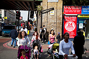 Young mothers push their babies in prams on Brixton Road, a multicultural area in South London. This is on the corner of Atlantic Road underneath the railway bridge. Brixton is a district in south London, England, in the London Borough of Lambeth. The area is identified in the London Plan as one of 35 major centres in Greater London. Brixton is predominantly residential with a prominent street market and substantial retail sector. It is a multiethnic community, with around 24 percent of Brixton's population being of African and Caribbean descent, giving rise to Brixton as the unofficial capital of the British African-Caribbean community.