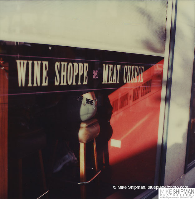A woman is seen seated at a wine shop through a large window. Polaroid.