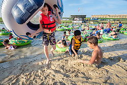 """Kids playing on beach surrounded by people in floating tubes at the """"Rockin' the River"""" July 4th celebration on the Trinity Trails at the Panther Island Pavilion, Trinity River, Fort Worth, Texas, USA."""