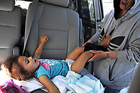 Victoria Pence changes Adalasia, 2, in their van, temporarily parked at the Exxon station in Salinas.
