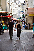 A couple touch fingers as they stroll through the market on the Rue Mouffetard. <br /> Rue Mouffetard is in the Fifth (cinquieme) arrondisement and the street is one of the oldest in Paris. A Roman road, it originally ran from the Roman Rive Gauche city all the way to Italy. Today, the market is famous for it's quality fresh produce and artisanal food shops.