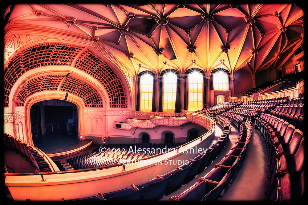 The University of Colorado Boulder's Macky Auditorium Concert Hall, with architectural lines highlighted by streams of warm sunlight.