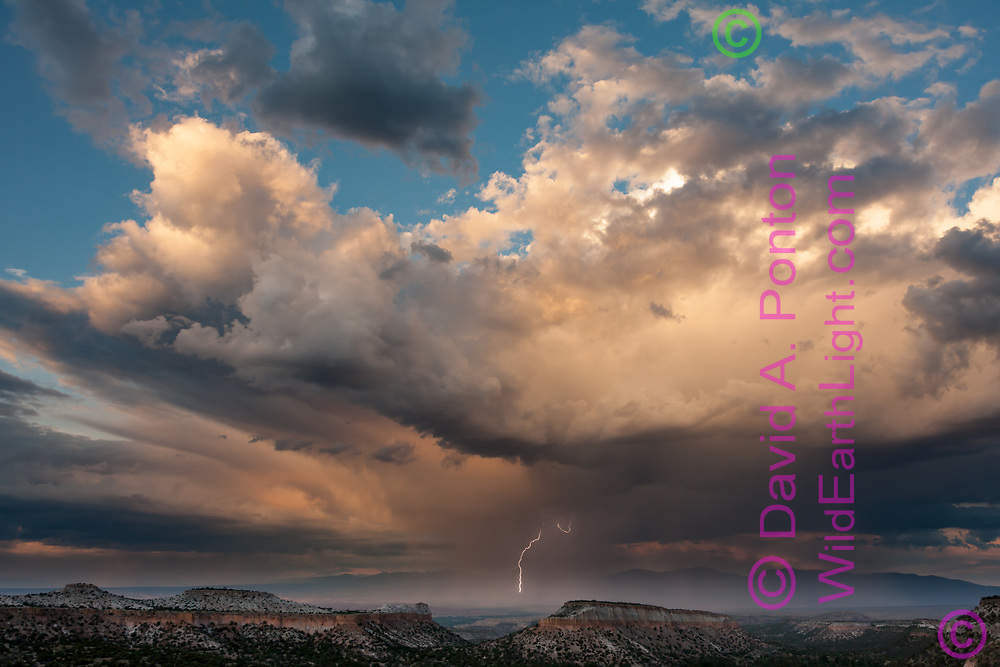 Rainstorm with lightning over the northern Rio Grande Valley at sunset, with mesas from the Pajarito Plateau in the foreground. East of Los Alamos, Jemez Mountains, New Mexico, America, © David A. Ponton
