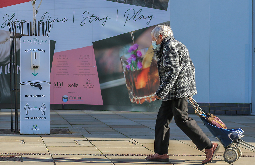 27th February, Cheltenham, England. A shopper walks past a hand sanitiser station setup in the Brewery Quarter during the third national lockdown.