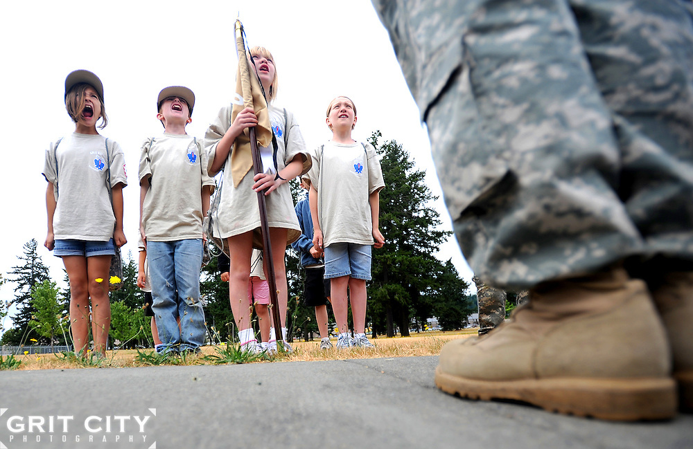 """Lauren Kirschner, l-r, Dalton Brewington, Michaela Hamel, and Ashleigh Wheeler shout """"Fire in the hole!"""" in response to their commander, Sgt. Russell Ho's, call to attention during the deployment camp."""