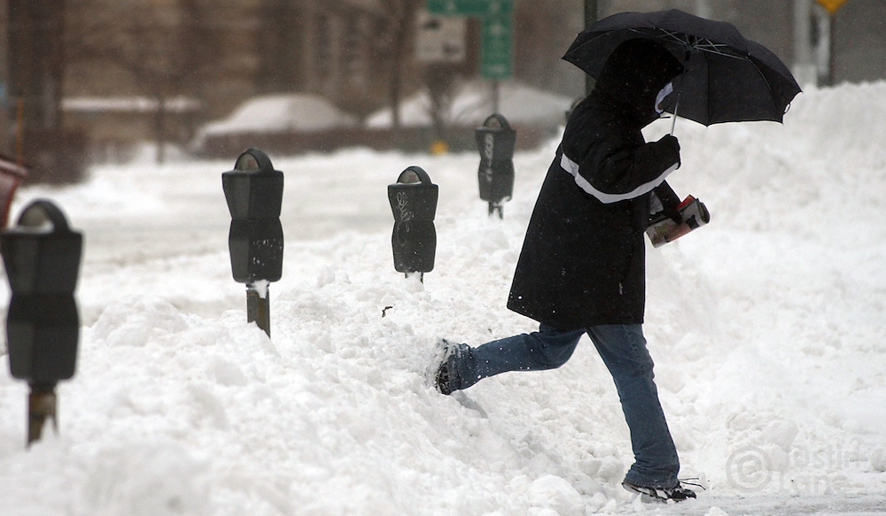 A pedestrian is seen traversing a high snow bank following a major winter storm in Brooklyn, NY Sunday, 23 January 2005. The storm dumped over a foot of snow, up to three in some places, on the Eastern United States, causing nearly 500 flights to be canceled Sunday morning at the New York metropolitan area's Newark, Kennedy and LaGuardia airports.