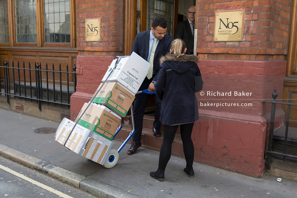 A male employee of a Barristers helps a woman colleague with a boxes of legal documents into the chambers address in the City of London, the capital's financial district, on 25th March 2019, in London, England.