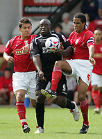 Photo: Paul Thomas.<br /> Walsall v Swansea. Coca Cola League 1.<br /> 27/08/2005.<br /> <br /> Adebayo Akinfenwa tries to get past Kris Taylor and Chris westwood.