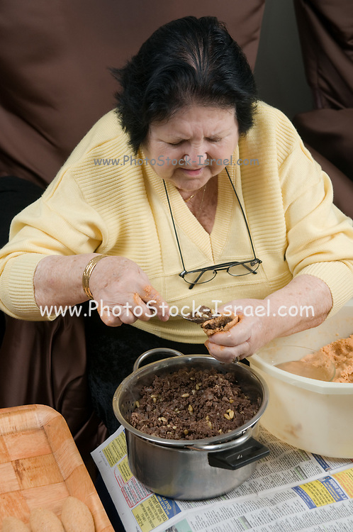 Preparing Kibbeh (Also Kibbe, Kubbah, Kubbeh) Burghul shell stuffed with chopped meat, onions and pine nuts. stuffing the burghul shell with the cooked meat mixture . Model Release available