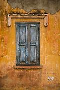 Blue shutters over a window in a yellow wall, Battambang Town Centre, Battambang, Cambodia