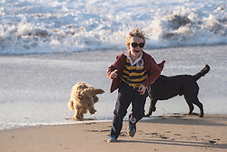 A young boy playing on Fistral Beach in Newquay, Cornwall.