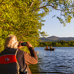 A man uses his cell phone to photograph two women paddling a canoe in the morning on Silver Lake in Piscataquis County, Maine. Near Greenville.