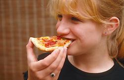 Teenage girl eating slice of pizza,