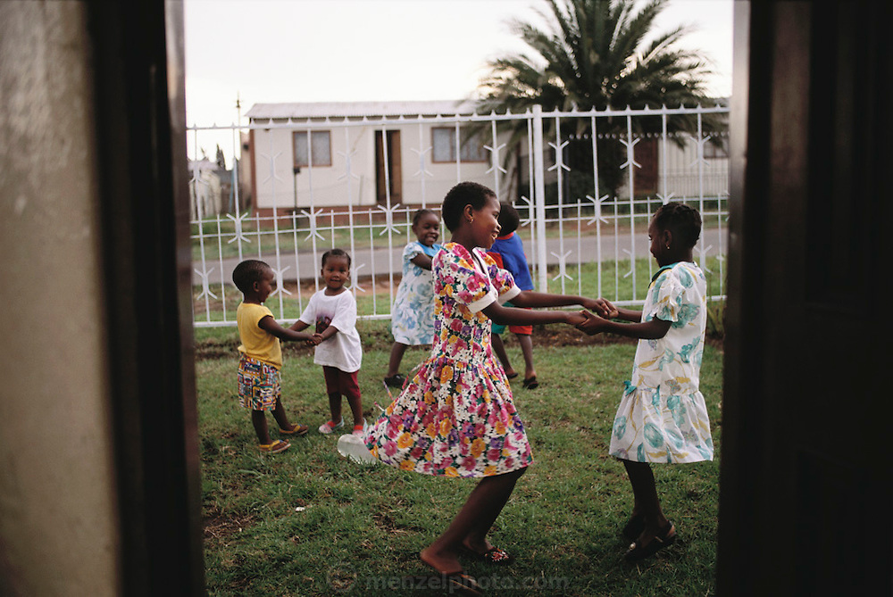 The Quampie children and a few of their friends play 'ring around the rosie? on a Sunday afternoon in front of their house in Soweto, South Africa.  The Qampie family lives in a 400 square foot concrete block duplex house in the sprawling area of Southwest Township (called Soweto), outside Johannesburg (Joberg) South Africa. Material World Project.
