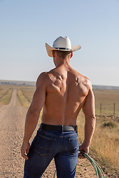 Back of a muscular cowboy without a shirt on a dirt road