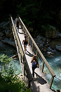 Visitors cross a bridge over the river Tolminka river at Tolminska Korita, on 20th June 2018, in Tolmin Gorge, Slovenia.