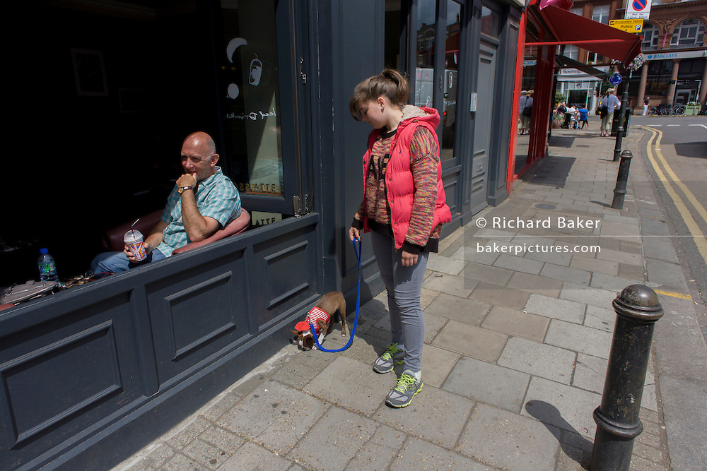 A dog owner and her small puppy stops to sniff where a customer sits outside a cafe, on a walk through a south London street.