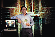 At U.C. Berkeley, graduate student Bill Tand holds a wafer with thousands of micromotors like the one he designed seen on the video and rear-screen projected behind him: a 200 micron linear resonator. Model Released [1990]