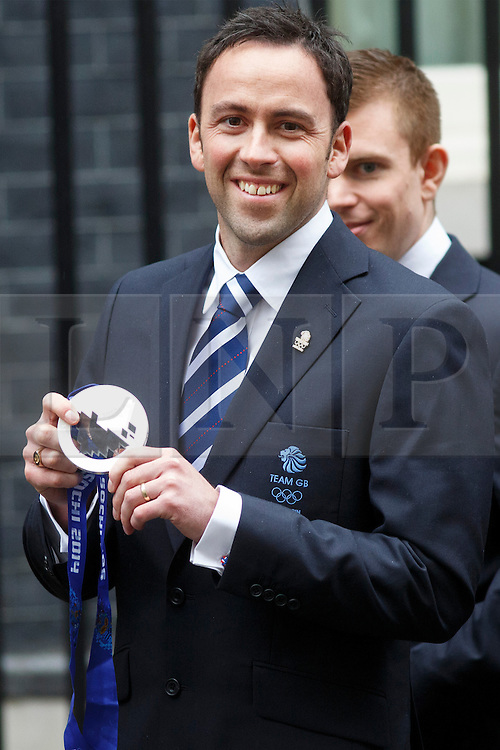 © licensed to London News Pictures. London, UK 25/02/2014. Men's curling silver medalist, Dave Murdoch poses with his medal as Winter Olympic medal winners of Team GB visiting Downing Street to meet Prime minister David Cameron on Tuesday, 25 February 2014 after their success in the Sochi 2014 Winter Olympics. Photo credit: Tolga Akmen/LNP