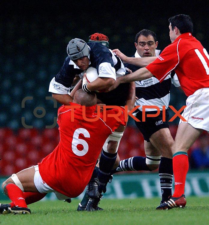 Barbarians' Kieran Roche is tackled by Wales' Gavin Thomas (l) and Craig Morgan (r)