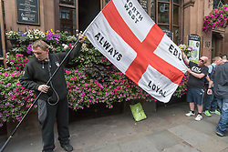 June 24, 2017 - London, UK - London, UK. 24th September 2017. Two of the around 40 EDL protesters get their flag ready outside the Wetherspoons pub on Whitehall. Later police escorted them to Charing Cross and down a backstreet to the Embankment where they were to hold a rally. Earlier police had moved several hundred anti-fascist counter-protesters organised by UAF from their route down to a separate area of the Embankment a short distance away where they continued to protest noisily against the EDL until the police escorted them back to Charing Cross station. Both EDL and UAF had conditions for their protests imposed on them under Section 12 and 14 of the Public Order Act, 1986, due to concerns of serious public disorder, and disruption to the community. Peter Marshall ImagesLive (Credit Image: © Peter Marshall/ImagesLive via ZUMA Wire)
