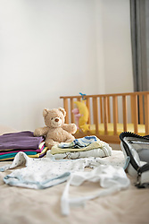 Still life baby clothes cot suitcase packing