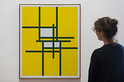 """© Licensed to London News Pictures. 29/10/2020. LONDON, UK.  A staff member poses next to """"Ohne Titel"""", 1953, by Verena Loewensburg. Preview of """"Female Minimal:  Abstraction in the Expanded Field"""", an exhibition of geometric abstract art at Galerie Thaddeus Ropac in Mayfair.  On display are works by 13 female artists from 10 countries many of whom were previously written out of art history due to their gender or politics at the time.  The show suns 29 October to 18 December.  Photo credit: Stephen Chung/LNP"""