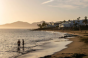 Two men stand in the sea on a quiet beach at sunset in Puerto Del Carmen, Lanzarote, Spain on 21st November 2020. Beaches across the island are nearly deserted since tourism plummeted due to Covid restrictions elsewhere in Europe. Although the Canary Islands have been relatively unscathed by the virus, with 155 lives lost from 2.1 million residents, the region is heavily dependent on tourism and locals are hoping that numbers recover as lockdown measures ease and vaccines potentially reduce the numbers of infections.