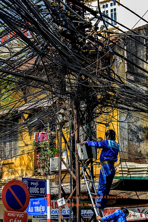 Organized Confusion: Electricians attempt to bring order to an seemingly incomprehensible number of electrical wires, Hanoi Vietnam.