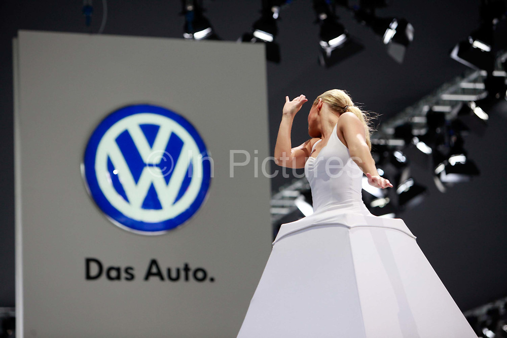 A woman performs in front of the Volkswagen AG logo during the China ( Guangzhou) International Automobile Exhibition in Guangzhou, Guangdong Province, China, on Monday, Nov. 21, 2011. Despite signs of slowing, China remains the largest and fastest growing market for international car makers, especially in the luxury sector.