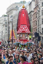 © licensed to London News Pictures. London, UK 17/06/2012. Three 40-foot high colourful chariots being pulled in Piccadilly as people celebrating Hare Krishna, an old Hindu tradition in central London, today (17/06/12). The giant chariots being accompanied by a procession of singers, musicians, and dancers as well as huge crowd. Photo credit: Tolga Akmen/LNP
