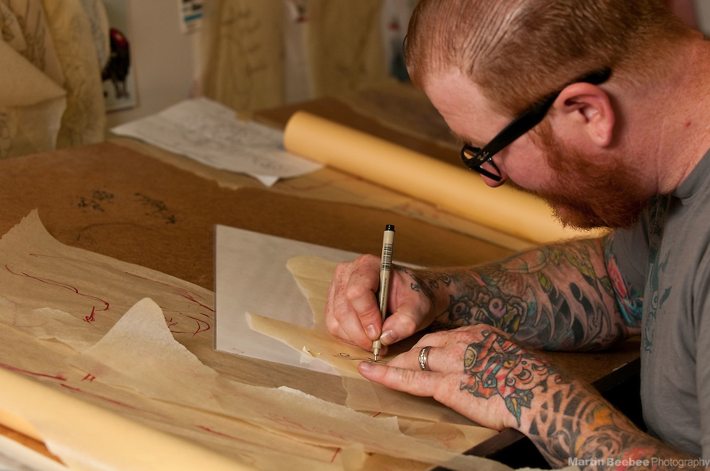 A tattoo artist (Justin Shaw of Faith Tattoo) sketches out a tattoo design for a client