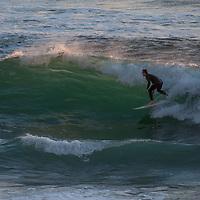 A surfer rides a wave at Montara State Beach on the California Coast