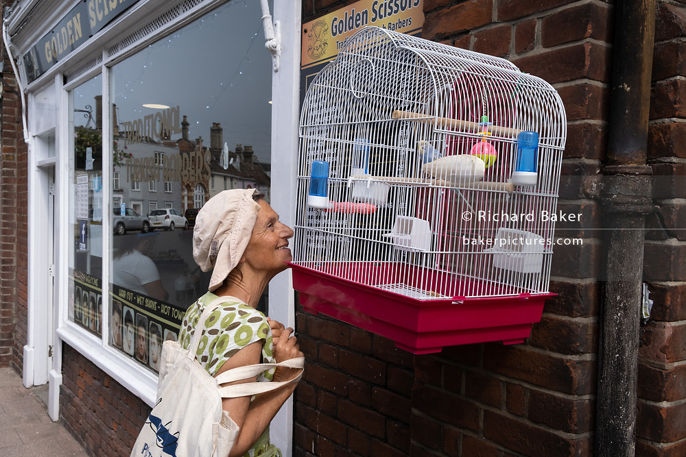 A passer-by notices a caged pet budgie hanging outside Turkish barbers 'Golden Scissors', on Earsham Street, on 13th August 2020, in Bungay, Norfolk, England.
