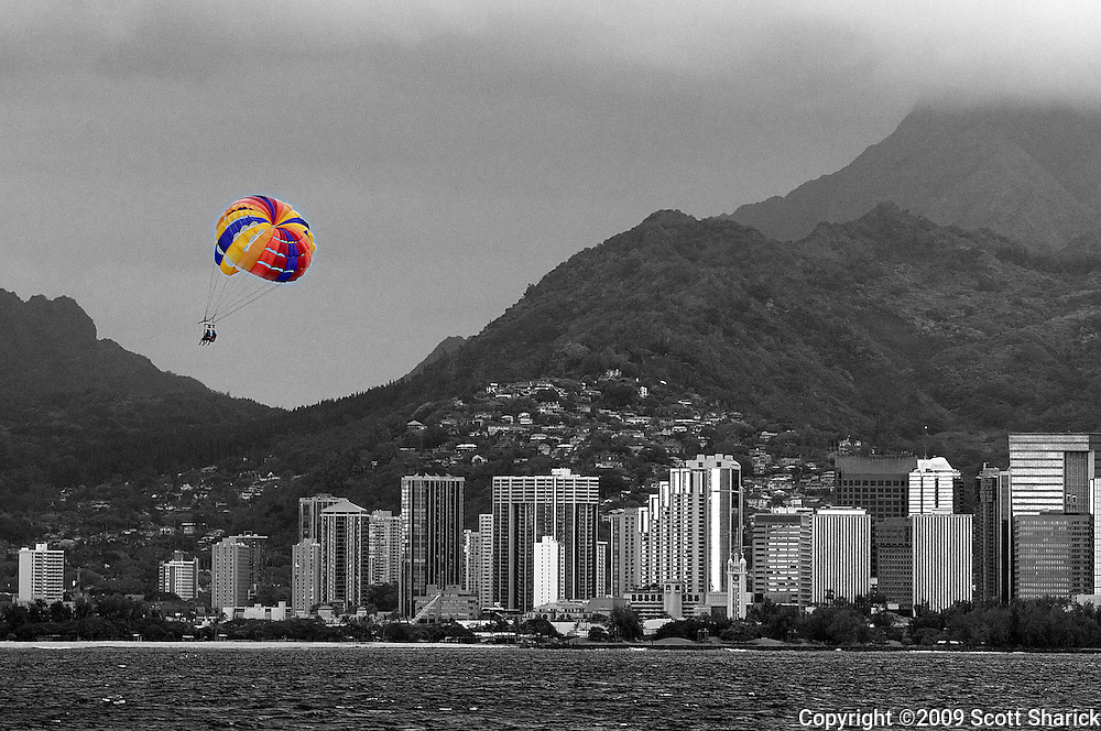 A colorful para sail floats in front of a black and white image of downtown Honolulu.