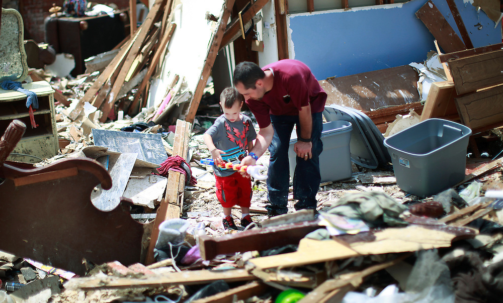 Justin Stephan (R) explains to his son Timothy, 3, that he can't play with a toy of his that he found in his tornado-destroyed home on 6th Avenue in Moore, Oklahoma May 23, 2013. The tornado was the strongest in the United States in nearly two years and cut a path of destruction 17 miles long and 1.3 miles wide. REUTERS/Rick Wilking (UNITED STATES)