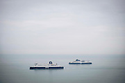 Cross channel ferries DFDS seaways pass each other outside the port of Dover, United Kingdom.  They cross the 34 kilometres 21 miles  distance of the English Channel, one of the busiest shipping lanes in the world as they transport vehicles and cargo between the ports of Dover, England and Calais, France.