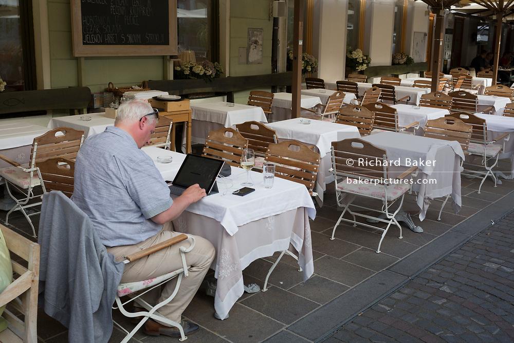 A man works alone at a riverside restaurant on Cankarjevo Nabrezje in the Slovenian capital, Ljubljana, on 25th June 2018, in Ljubljana, Slovenia.