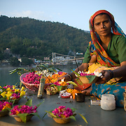 a woman selling flowers for puja on the banks of the Ganga (Ganges) river in Rishikesh