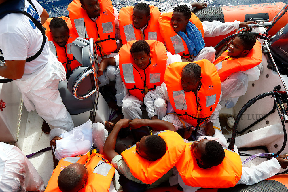 Migrants sit in a Migrant Offshore Aid Station (MOAS) RHIB (rigid hulled inflatable boat) alongside the MOAS ship MV Phoenix before being transferred to an Italian Coast Guard vessel, after being rescued some 20 miles (32 kilometres) off the coast of Libya, August 3, 2015.  118 migrants were rescued by MOAS from a rubber dinghy off Libya on Monday morning . The Phoenix, manned by personnel from international non-governmental organisations Medecins san Frontiere (MSF) and MOAS, is the first privately funded vessel to operate in the Mediterranean.<br /> REUTERS/Darrin Zammit Lupi <br /> MALTA OUT. NO COMMERCIAL OR EDITORIAL SALES IN MALTA