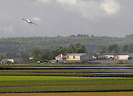 Goshen, New York - A crop duster sprays herbicide while flying over a black dirt fields planted with onions and barley on May 21, 2011. The pesticide kills the barley, which was planted with onions in the field to shield the onions from the wind. The barley grows faster but then has to be killed.
