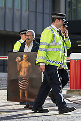 © Licensed to London News Pictures . 06/07/2016 . London , UK . Artist KAYA MAR with a satirical painting of Tony Blair outside the venue . The families of those killed in the Iraq war arrive at the QEII Centre . Scene outside the Queen Elizabeth II Conference Centre in Westminster , ahead of the publication of the Chilcot Inquiry's report in to the 2003 invasion of Iraq . Photo credit : Joel Goodman/LNP